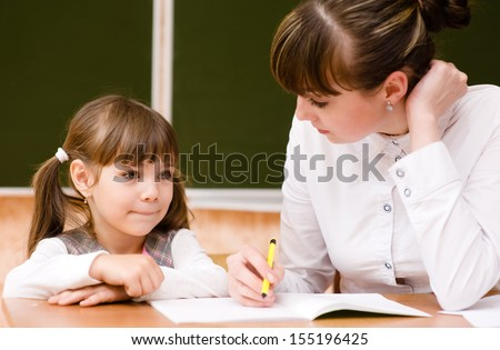 Teacher helps the student with schoolwork in  classroom - stock photo