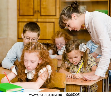 Teacher helps the student with schoolwork in school classroom - stock photo