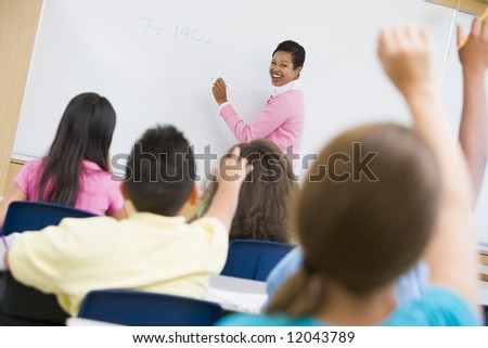 Teacher holding elementary school maths class - stock photo