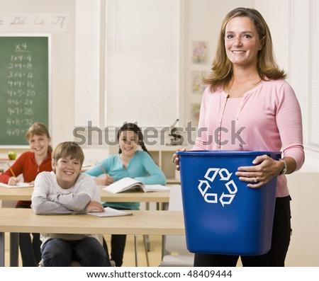 Teacher holding recycling bin - stock photo