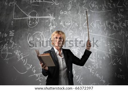 Teacher in a classroom holding a book - stock photo