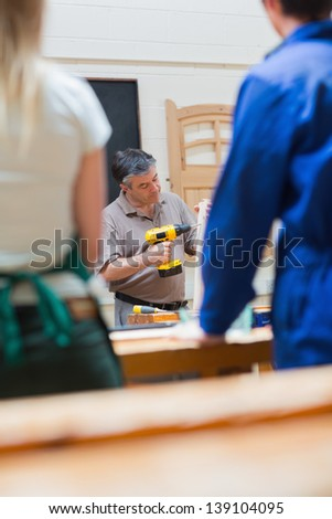 Teacher in a woodwork class holding a wooden board while explaining and drilling - stock photo