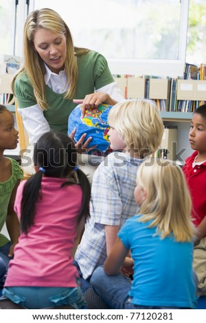 Teacher in class showing students a globe (selective focus) - stock photo