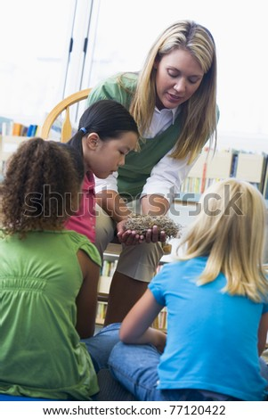 Teacher in class showing students a nest - stock photo