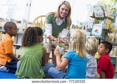 Teacher in class showing students bamboo plant