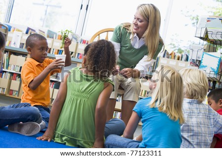 Teacher in class showing students bamboo plant - stock photo