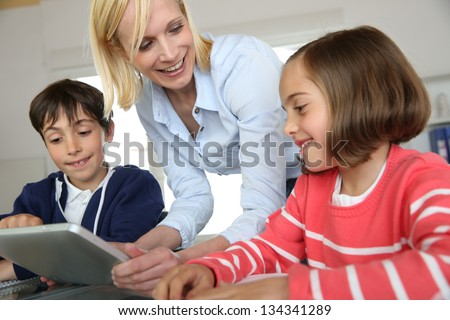 Teacher in class with kids using electronic tablet - stock photo