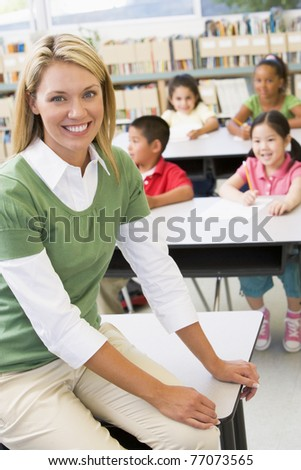 Teacher in class with students in background (selective focus) - stock photo