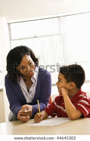 Teacher in classroom helping boy with schoolwork. Vertically framed shot. - stock photo
