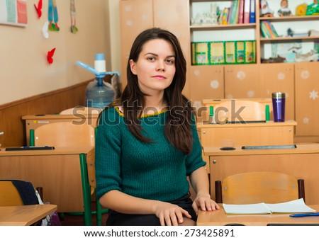 teacher in classroom near desks - stock photo