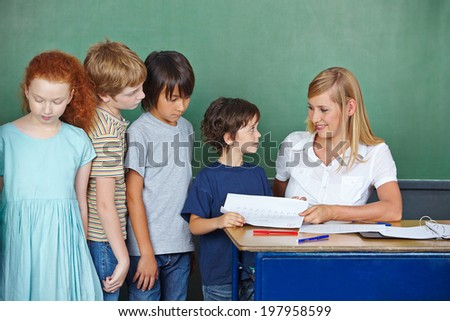 Teacher in elementary school giving her students tests back