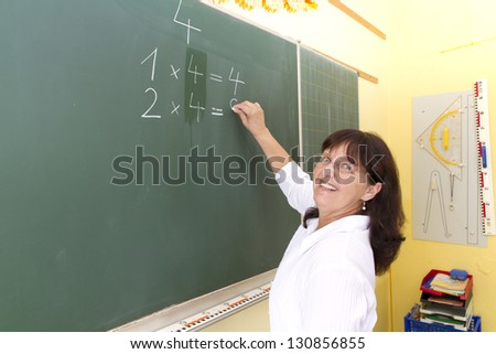 Teacher in front of a blackboard in school. - stock photo