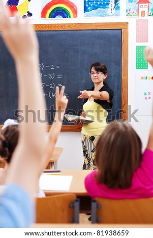 Teacher in front of chalkboard, pointing at students who raised their arms