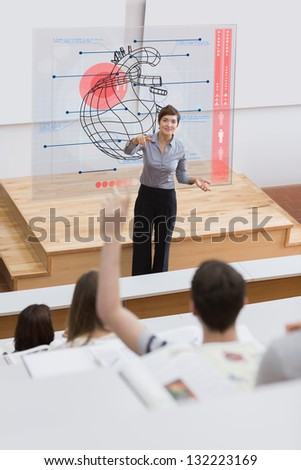 Teacher in front of futuristic interface pointing a student who is raising his hand - stock photo