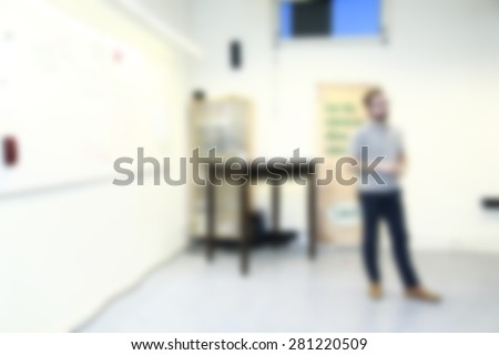 teacher in front of the class explaining ,blurred background - stock photo