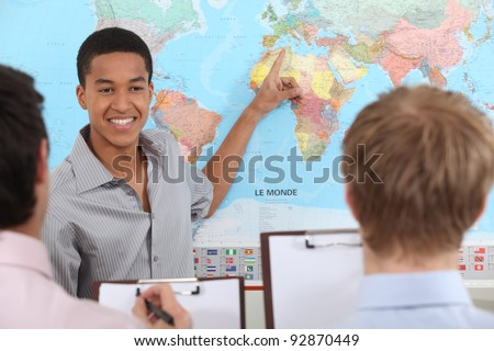 Teacher in geography class - stock photo