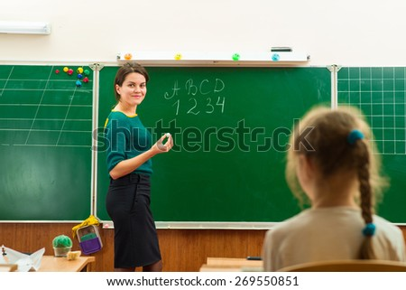teacher in the classroom writing on the chalkboard
