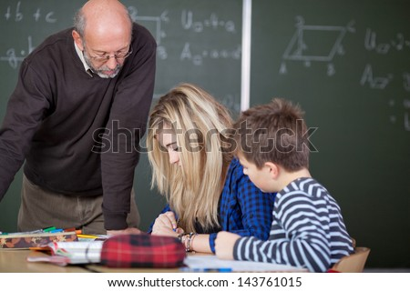 Teacher is checking on the work of his students - stock photo