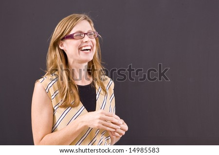 Teacher laughing in front of the class(open copy space).