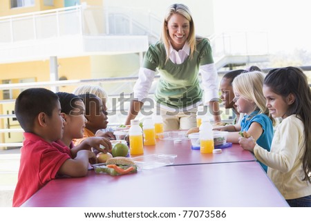 Teacher leaning on table outdoors while students eat lunch (high key) - stock photo