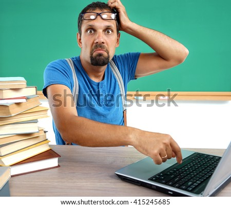 Teacher looking at camera with an expression of incomprehension face. Photo of man working at computer, education concept - stock photo
