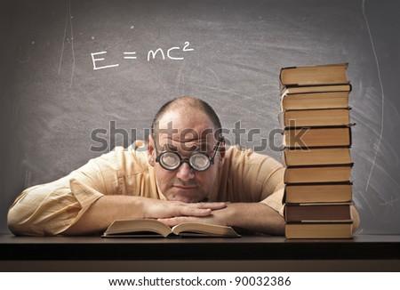 Teacher lying on a desk in a classroom - stock photo