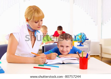 teacher makes the lessons with their children in school. - stock photo