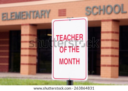 Teacher of the month parking spot.  Focus is on the sign with the school building in the background. - stock photo