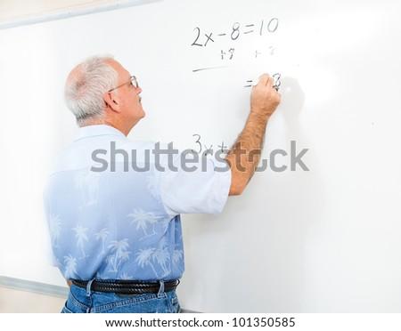 Teacher or adult student writing an algebra problem on the blackboard. - stock photo