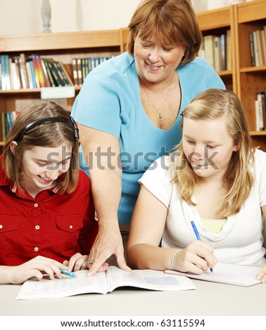 Teacher or librarian in the school library, helping teenage students with their homework. - stock photo