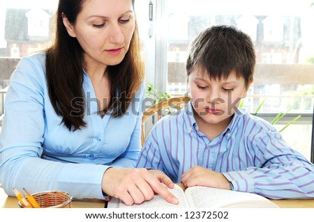 Teacher or tutor helping school boy to study - stock photo