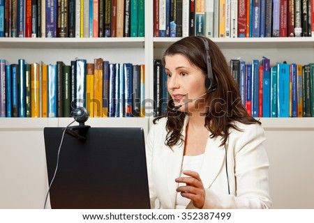 Teacher or tutor of a distance university giving an online lecture or webinar her office, mooc - stock photo