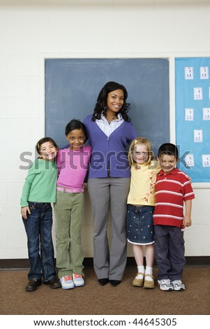 Teacher posing for group portrait with students in school classroom. Vertically framed shot. - stock photo