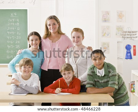Teacher posing with students - stock photo