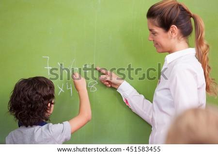 Teacher questioning kid at chalkboard. - stock photo