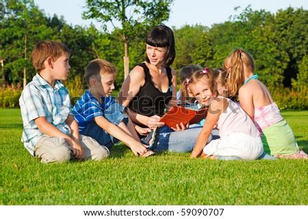 Teacher reading book to preschool kids - stock photo