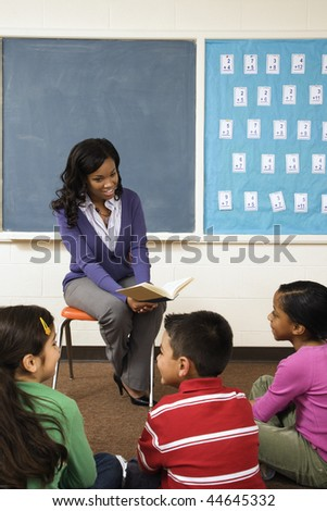 Teacher reading book to young students in classroom. Vertically framed shot. - stock photo