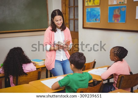 Teacher reading out loud to classroom at the elementary school - stock photo