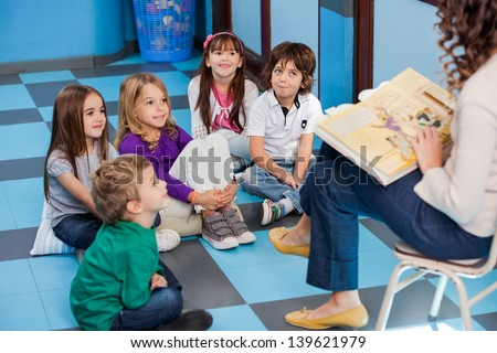 Teacher reading story book to children in kindergarten - stock photo