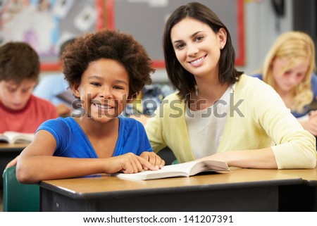Teacher Reading With Female Pupil In Class - stock photo