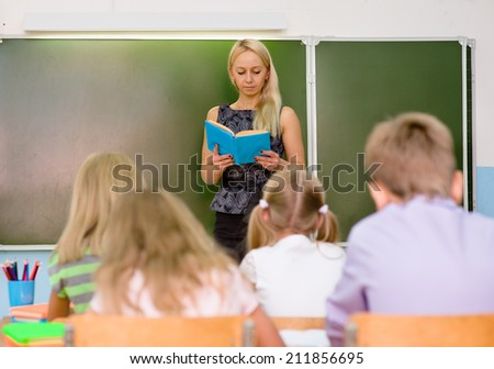 teacher reads the students a book - stock photo