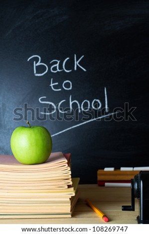 Teacher's desk with a pile of books, an apple and other equipment.  The words 'Back to School' written in chalk on the blackboard in soft focus background.