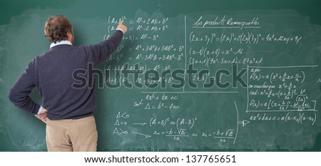 Teacher showing figures on the blackboard - stock photo