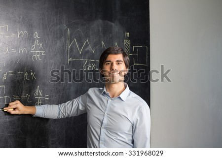 Teacher showing formulas on the blackboard - stock photo