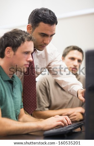 Teacher showing something on screen to mature students in the computer room - stock photo
