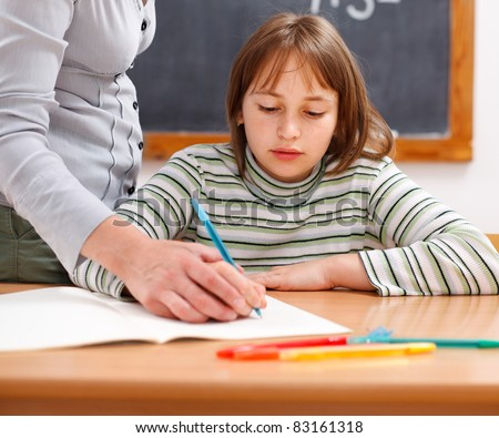 Teacher showing writing by holding hand of elementary school student - stock photo