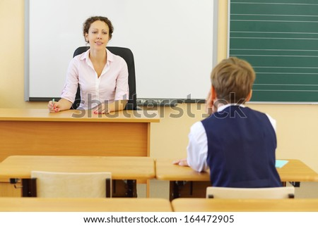 Teacher sits at table and boy sits at desk and looks at her in classroom at school. Focus on woman.