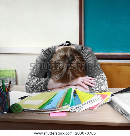Teacher sits in classroom setting head on hands - stock photo