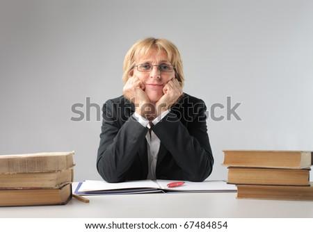 Teacher sitting at a desk - stock photo