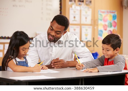 Teacher sitting at desk with two elementary school pupils - stock photo